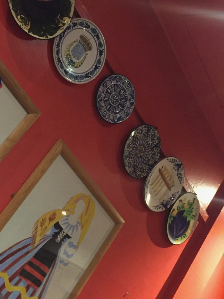 A red wall at Meson don Felipe. Showing some Spanish plates and a picture of a woman in Spanish dress.