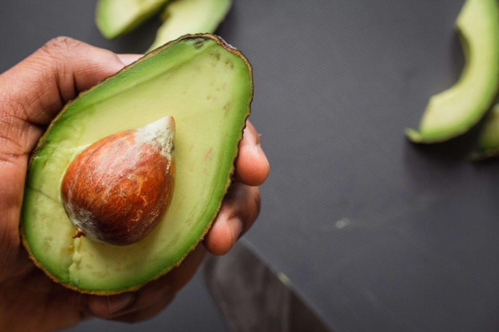 Someone holding half an avocado in their hand. Other pieces of avocado can be seen.