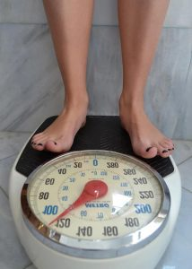 A person standing on some analogue scales