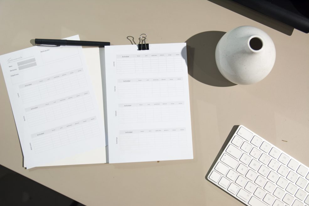 A planner and pen, a keyboard and a vase.