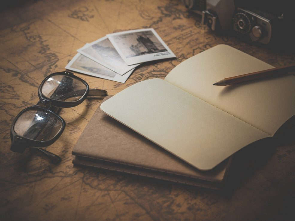 Glasses, photos and a notebook and pen