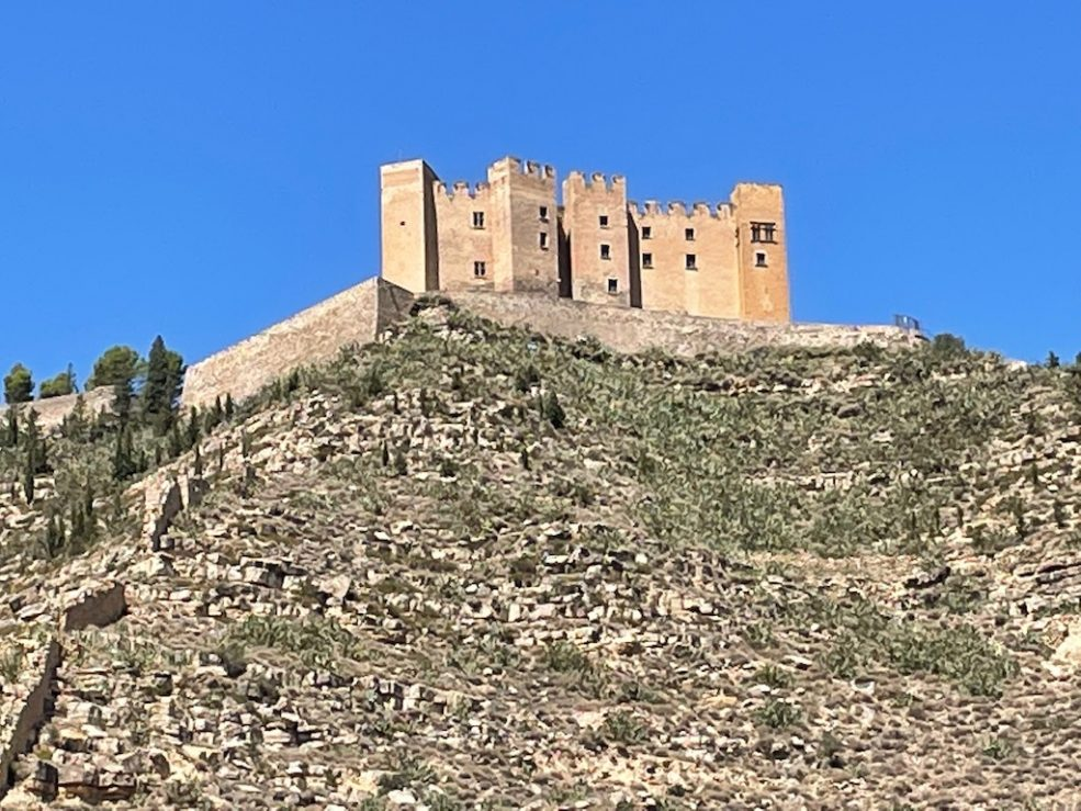 Castle stands on top of a hill. There is very little on the hill except brown rock. The sky is very blue.